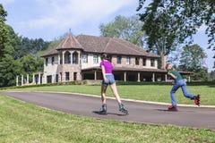 女孩直排轮式溜冰鞋滑冰 免版税库存图片