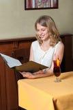 女孩读文件事假咖啡店和微笑 免版税库存图片