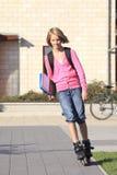 女孩滑旱冰到学校 免版税库存照片