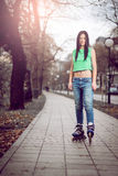 女孩滑旱冰在公园 免版税库存照片