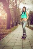 女孩滑旱冰在公园 库存图片