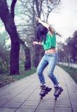 女孩滑旱冰在公园 库存照片