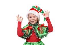 女孩-显示符号OK的圣诞老人的矮子。 免版税图库摄影