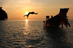 女孩从有日落的一条长尾巴小船跳 免版税图库摄影