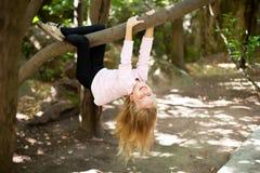 女孩从树垂悬 免版税图库摄影