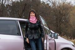女孩从桃红色汽车出去 免版税库存照片