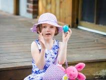 女孩阻止一个蓝色复活节彩蛋 免版税库存图片