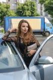 女孩从汽车出来 免版税库存照片