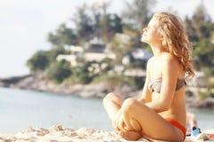女孩以海滩的金黄卷毛基于 库存图片