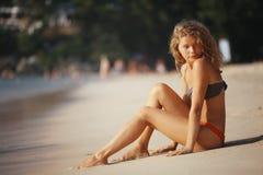 女孩以海滩的金黄卷毛基于 免版税库存图片