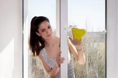 女孩洗涤一个窗口 库存照片
