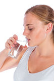 女孩从玻璃的饮料水 免版税库存照片