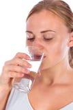 女孩从玻璃的饮料水 库存图片