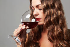 女孩玻璃红葡萄酒 美丽的白肤金发的饮用的红葡萄酒妇&# 库存照片