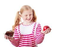女孩从甜蛋糕和红色苹果选择 免版税图库摄影