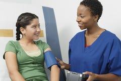 女孩医生的检查的血压 图库摄影
