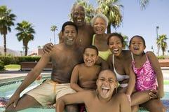 女孩(5-6)男孩(7-9)男孩(10-12)有父母和祖父母的游泳池正面图画象的。 库存照片