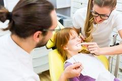 给女孩治疗的牙医 免版税库存照片
