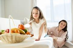 女孩从篮子的采摘蜜桔与后边母亲 免版税图库摄影