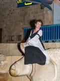 女孩-耶路撒冷俱乐部的骑士的成员,打扮在中世纪夫人的传统服装,坐公牛雕象a 免版税图库摄影
