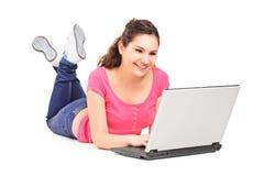 女孩说谎在地板上和与膝上型计算机一起使用 免版税库存照片