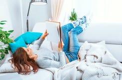 女孩读说谎在沙发的一本书 免版税库存图片