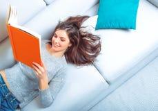 女孩读说谎在沙发的一本书 库存照片