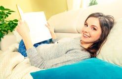 女孩读说谎在沙发的一本书 免版税库存照片