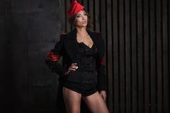 女孩画象一件黑飞行员制服的有帽子的 免版税库存图片