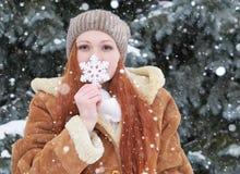 女孩画象在室外的冬天,多雪的天气,显示大雪花玩具 免版税库存照片