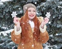女孩画象在室外的冬天,多雪的天气,显示大雪花玩具 免版税库存图片