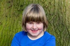 女孩画象在橡木树干前面的与吠声 免版税库存照片