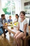 女孩画象坐餐桌,当家庭吃早餐在背景时 图库摄影