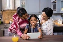 女孩画象有使用数字式片剂的母亲和祖母的在厨房 库存照片
