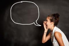 女孩画象有讲话泡影的在黑板 库存图片