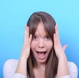 女孩画象有震动姿态的反对蓝色背景 免版税库存照片