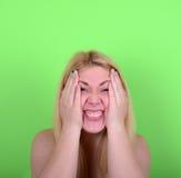 女孩画象有滑稽的面孔的反对绿色背景 免版税库存图片