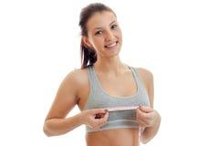 女孩画象炫耀与测量的磁带的一个特写镜头在乳房 免版税库存图片