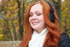 女孩画象,在城市公园、秋天季节、黄色树和下落的地方教育局听在音频球员的音乐有耳机的,坐长凳 免版税库存照片