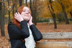 女孩画象,在城市公园、秋天季节、黄色树和下落的地方教育局听在音频球员的音乐有耳机的,坐长凳 图库摄影