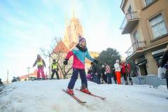 女孩滑雪在市中心 图库摄影