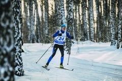 女孩滑雪者种族经典样式在桦树森林里在冬天 免版税库存图片