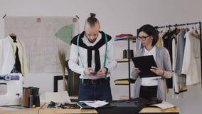 女孩` s助理,展示在纸片的设计师剪影 他的演播室照片的时装设计师 影视素材