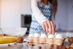女孩` s手的特写镜头在厨房里采取一个鸡蛋 免版税图库摄影