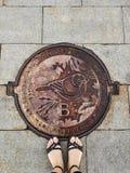 女孩` s脚在血污的Vorobyovy的下水道出入孔站立 在舱口盖的鸟是麻雀-地方的标志 库存照片