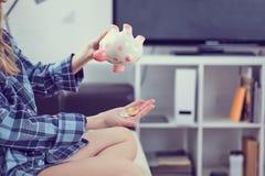 女孩` s递拿着存钱罐和倾吐bitcoins出于它 秋天的概念按cryptocurrency的价值 免版税图库摄影