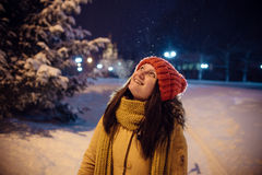 女孩` s画象在降雪期间的冬天,以教会、一根壮观的冷杉木和数字灯为背景 免版税库存图片