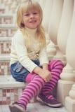 女孩3岁坐一个美丽的楼梯 免版税库存照片