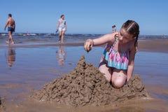 女孩bulding在海滩的沙堡 免版税图库摄影