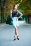 女孩fashoionable穿戴的摆在公园 库存图片